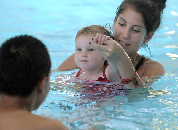 Swim instructor Leigha McCoy helps Maggie Burke, 26 months-old, with moving her arms while swimming towards instructor Josh Mak during the begining swim lessons at the Broomfield Community Center pool on Wednesday.<br /> <br /> June 22, 2011<br /> staff photo/David R. Jennings