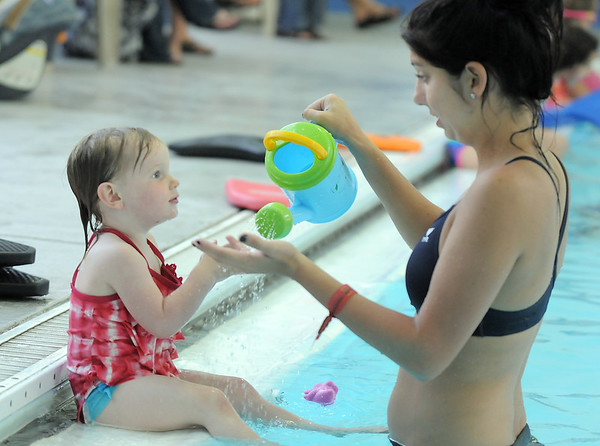 Swim instructor Leigha McCoy sprinkles water on Maggie Burke, 26 months-old, to get her used to water during the beginning swim lessons at the Broomfield Community Center pool on Wednesday.<br /> <br /> June 22, 2011<br /> staff photo/David R. Jennings