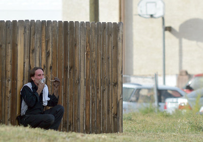 An employee of East of Sweden upset after a fellow employee was shot and killed, sits by a nearby fence across from the business in Broomfield. October 12, 2012 staff photo/ David R. Jennings