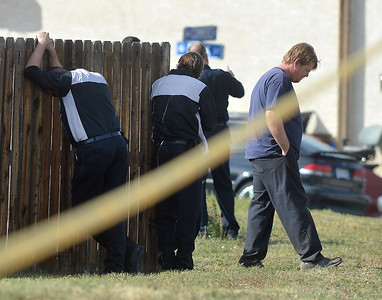 Employees  of East of Sweden Saab repair stand near a fence at 155 Commerce St. after a fellow employee was shot and killed in Broomfield. October 12, 2012 staff photo/ David R. Jennings