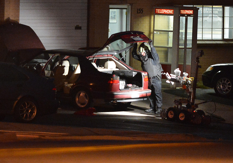 An Adams County Bomb Squad officer searches the contents of a possible suspects car for a bomb at the scene of a fatal shooting at 155 Commerce St. on Friday in Broomfield.<br /> October 12, 2012<br /> staff photo/ David R. Jennings