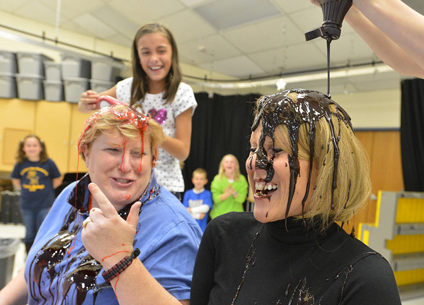 Mountain View Elementary School principal Tracey Amend, right, and assistant principal Shelley Stetler have banana split toppings of strawberry and chocolate poured on their heads by 5th grader Ashley Becker, left,  and 4th grader Brett Kaufman during an assembly at the school on Friday. The principals agreed to the stunt if 100 or more students ran a 1k or 5k for a fundraising event last October.<br /> <br /> November 30, 2012<br /> staff photo/ David R. Jennings