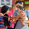 be0719cuddle06.JPG Archana Gopal, left, and her husband Ramesh show their daughter Saanui, 8 months-old, a violin after the Cuddle Time Concert with the Broomfield Symphony Orchestra on Saturday.<br /> <br /> July 14, 2012<br /> staff photo/ David R. Jennings