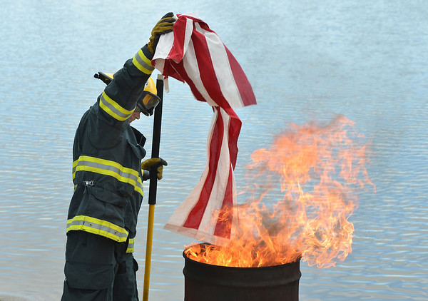 be0617flag16.jpg North Metro Fire Rescue paramedic Randy Delaney places the strips from a flag into the fire during Thursday's 8th Annual Flag Retirement Ceremony at the Community Park Amphitheater.<br /> June 14, 2012 <br /> staff photo/ David R. Jennings
