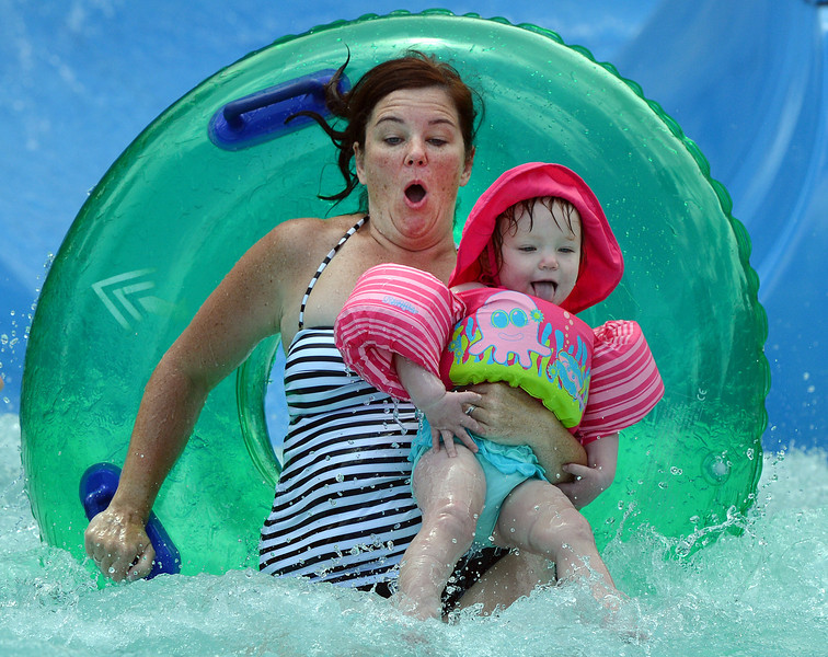 "be0705thebay02.JPG Kerry Carter and her daughter Catherine, 1 1/2, splash in the pool of the big blue slide while enjoying the fun and cooling off at The Bay Aquatic Center on Saturday.<br /> <br /> June 30, 2012<br /> staff photo/ David R. Jennings<br /> <br /> for more photos and video please go to  <a href=""http://www.broomfieldenterprise.com"">http://www.broomfieldenterprise.com</a>"