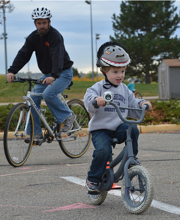 Daniel Pelham rides his bicycle with his son, Julian, 3 1/2, during the Bicycle Skills  Course sponsored by the Children's Health Advocacy Institute in the Bay Aquatic Park parking lot on Saturday.<br /> staff photo/ David R. Jennings