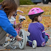 Gara Ball, 5, right, waits for her mother, Nicole, to  put the training wheels back on Gara's bicycle during the Bicycle Skills  Course sponsored by the Children's Health Advocacy Institute in the Bay Aquatic Park parking lot on Saturday.<br /> October 13, 2012<br /> staff photo/ David R. Jennings