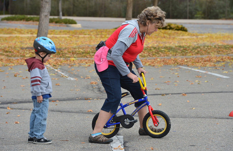 Joel Chambers, 4, left, watches volunteer Leslie Clark shows Joel how to ride his bicycle during the Bicycle Skills  Course sponsored by the Children's Health Advocacy Institute in the Bay Aquatic Park parking lot on Saturday.<br /> October 13, 2012<br /> staff photo/ David R. Jennings
