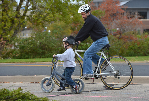 Daniel Pelham rides his bicycle with his son, Julian, 3 1/2, during the Bicycle Skills  Course sponsored by the Children's Health Advocacy Institute in the Bay Aquatic Park parking lot on Saturday.<br /> October 13, 2012<br /> staff photo/ David R. Jennings