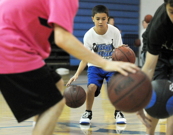 BE0610CAMP01<br /> Sean Duffy, 12, dribbles with two balls following the guidance of instructor Austin Wood, front, at the Big Blue Basketball Camp held by coach Terrance Dunn at Broomfield High School on Tuesday.<br /> <br /> June 8, 2010<br /> Staff photo/ David R. Jennings