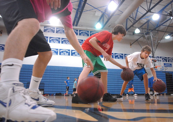 BE0610CAMP02<br /> Mike Loftus, 13, center, and Alec Mathews, 14, right,  work on their dribbling skills with instructor Austin Wood, left, at the Big Blue Basketball Camp held by coach Terrance Dunn at Broomfield High School on Tuesday.<br /> <br /> June 8, 2010<br /> Staff photo/ David R. Jennings