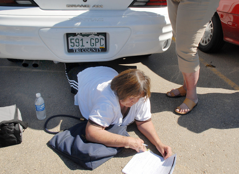 Mary Madrigal, of Ft. Lupton,  used a car for shade while waiting in line and filling out the short form  during Saturday's open casting call for The Biggest Loser 11 at Broomfield's 1st Bank Center.<br /> July 17, 2010<br /> Staff photo/ David R. Jennings