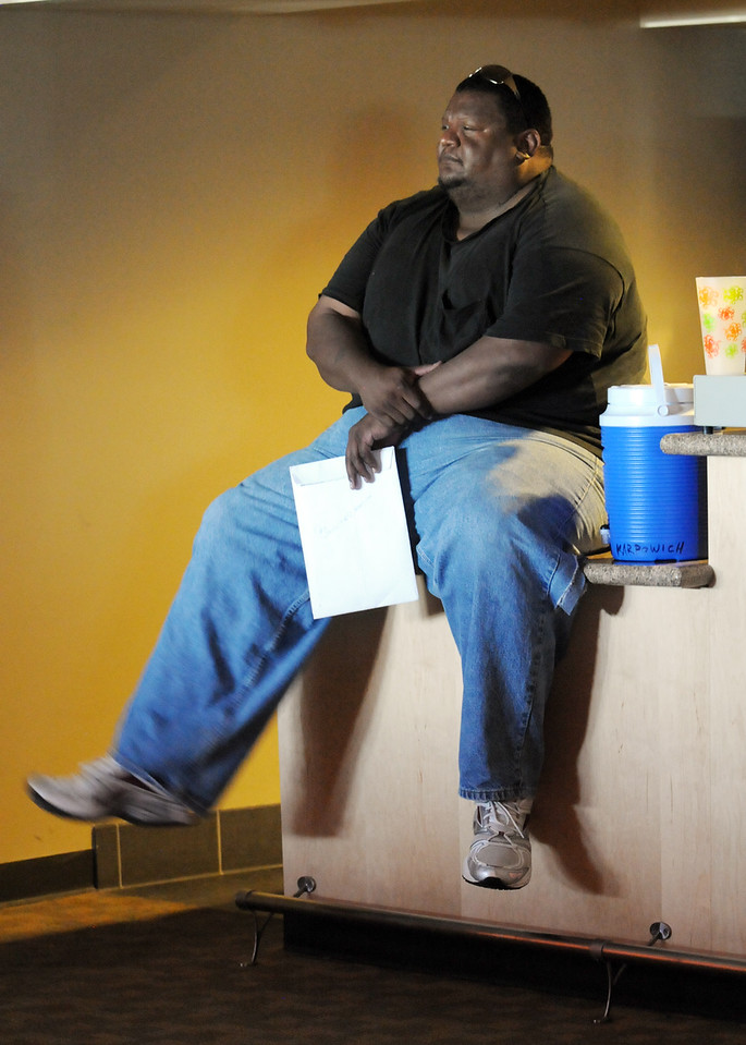 Jimmy Webb of Broomfield and former football player for CU sits on a concession booth counter while waiting to be interviewed  for Saturday's open casting call for The Biggest Loser 11 at the 1st Bank Center in Broomfield.<br /> July 17, 2010<br /> Staff photo/ David R. Jennings