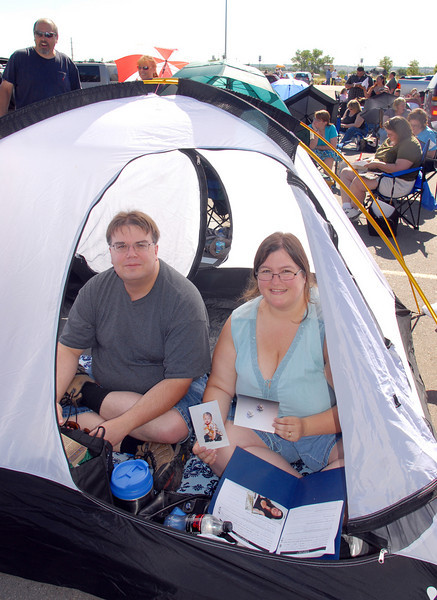 Erick and Kim Ellis, of Denver, used their tent for shade as they wait in line for Saturday's open casting call for The Biggest Loser 11 at Broomfield's 1st Bank Center. Kim holds a picture of her their son Aidan, who is their inspiration to apply for the show. <br /> July 17, 2010<br /> Staff photo/ David R. Jennings
