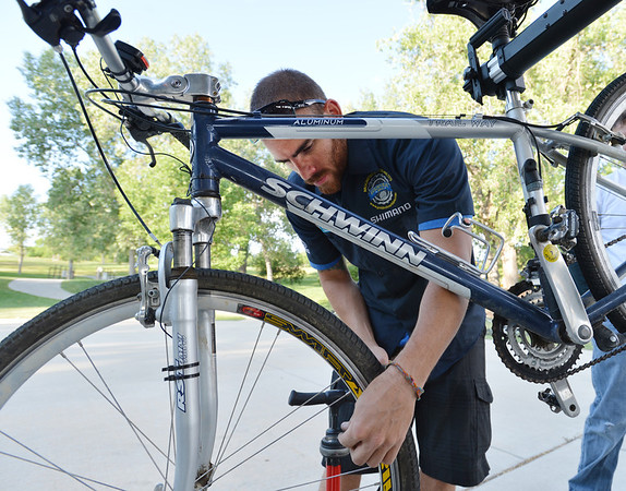 "Golden Bear Bikes mechanic Abe Martin, checks the air in a commuter's tire during Bike to Work Day at East Park on Wednesday.<br /> <br /> June27, 2012<br /> staff photo/ David R. Jennings<br /> <br /> for more photos and video please go to  <a href=""http://www.broomfieldenterprise.com"">http://www.broomfieldenterprise.com</a>"