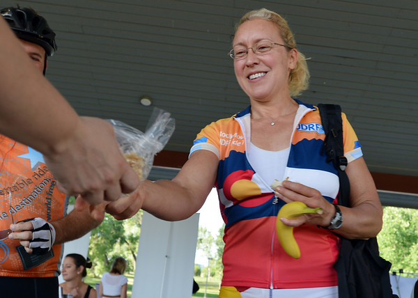 "Linda Kravets is handed food from Noodles & Company station during Bike to Work Day at East Park on Wednesday.<br /> <br /> June27, 2012<br /> staff photo/ David R. Jennings<br /> <br /> for more photos and video please go to  <a href=""http://www.broomfieldenterprise.com"">http://www.broomfieldenterprise.com</a>"