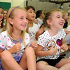 "First graders Ella Olmsted, left, and Lily Nielson gesture with the ""chicken"" song during the Welcome Rally at Birch Elementary School on Friday.<br /> <br /> August 21, 2009<br /> staff photo/David R. Jennings"