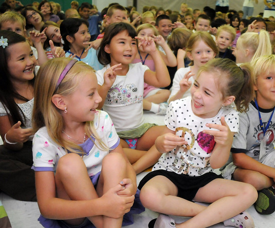 First graders Ella Olmsted, left, and Lily Nielson laugh during a song at the Welcome Rally at Birch Elementary School on Friday.<br /> <br /> August 21, 2009<br /> staff photo/David R. Jennings