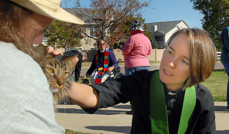 Mark Castleman holds his cat Harry as Rev. Kim Seidman, Holy Comforter Episcopal Church, does the blessing during the blessing of the animals on the front lawn of the church on Saturday.<br /> <br /> October 2, 2010<br /> staff photo/David R. Jennings