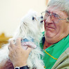 Reverand Dr. Rod Moore receives a little doggie kiss after blessing Addi Snow, owned by Sally Hoffman during the Blessing of the Animals and St. Francis Festival at The Church of the Holy Comforter on Saturday. Over 30 dogs, 1 cat and 1 gecko received the blessing in the church sanctuary.<br /> October 10, 2009<br /> Staff photo/David R. Jennings