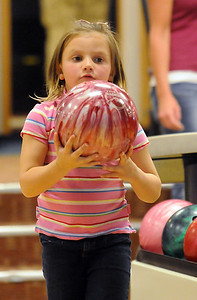 Avery Prochazka, 5, looks over the bowling ball while bowling for North Metro Fire during the Bowl for a Precious Child Broomfield Police vs. North Metro Fire Rescue District at Chippers Lanes on Sunday.  April 11, 2010 Staff photo/David R. Jennings