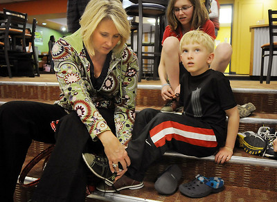Elizabeth Licht helps her son Clayton, 5, with his bowling shoes before bowling at the Bowl for a Precious Child Broomfield Police vs. North Metro Fire Rescue District at Chippers Lanes on Sunday.  April 11, 2010 Staff photo/David R. Jennings