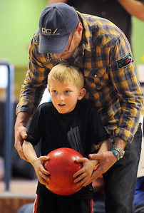 BE0415BOWL02 Paul Licht helps his son Clayton, 5, during the Bowl for a Precious Child Broomfield Police vs. North Metro Fire Rescue District at Chippers Lanes on Sunday.  April 11, 2010 Staff photo/David R. Jennings