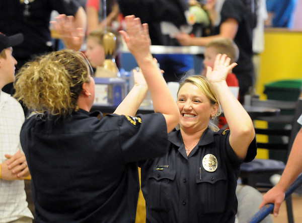 Broomfield officers Jennifer King, left, is given a cheer by Enea Hempelmann during the Bowl for a Precious Child Broomfield Police vs. North Metro Fire Rescue District at Chippers Lanes on Sunday.<br /> <br /> April 11, 2010<br /> Staff photo/David R. Jennings
