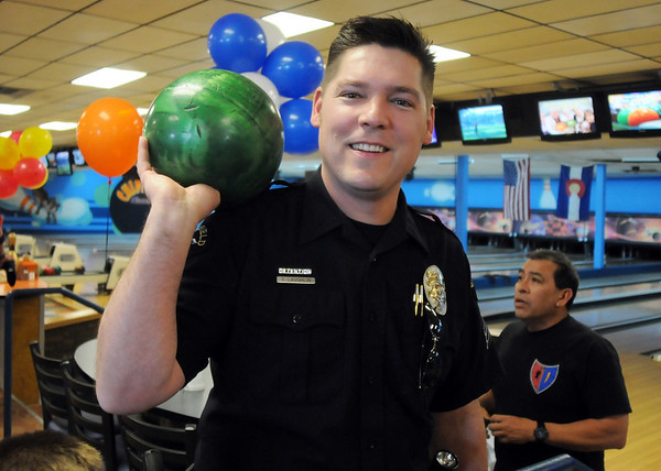 Broomfield Police officer Shawn Laughlin holds a bowling ball before the tournament, Bowl for a Precious Child Broomfield Police vs. North Metro Fire Rescue District, begins at Chippers Lanes on Sunday.<br /> <br /> April 11, 2010<br /> Staff photo/David R. Jennings