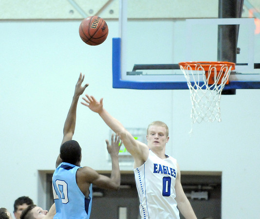 Broomfield's Dan Perse tries to block the shot by Widefield's Anthony Saunders during Friday's state playoff game at Broomfield.<br /> February 24, 2012 <br /> staff photo/ David R. Jennings