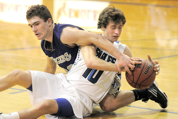 Broomfield's Austin Wood fights for possession of the ball with Holy Family's Connor Clay during Saturday's cross-town rivalry game at Broomfield.<br /> January 28, 2012<br /> staff photo/ David R. Jennings