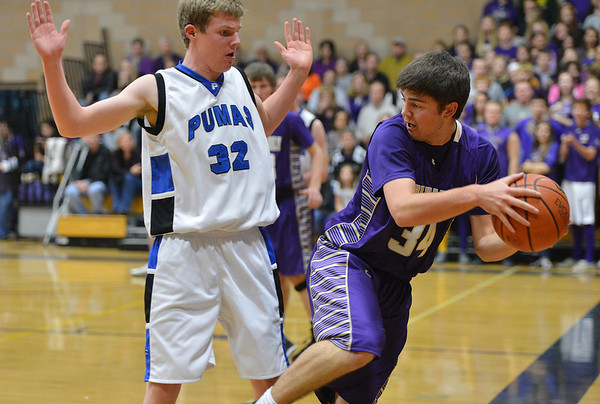 Holy Family's Devlin Granberg keeps  the ball in play past Peak to Peak's Andrew Otey during Friday's boys game at Peak to Peak.<br /> January 25, 2013<br /> staff photo/ David R. Jennings