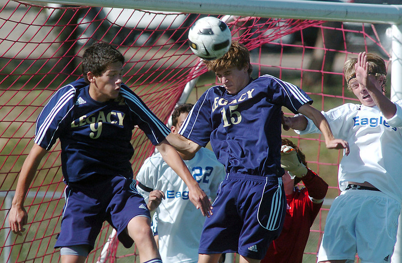 Legacy's Kyle Murrow , center, does a header to move the ball away from the goal  during Saturday's game at Elizabeth Kennedy Stadium.<br /> September 24, 2011<br /> staff photo/ David R. Jennings