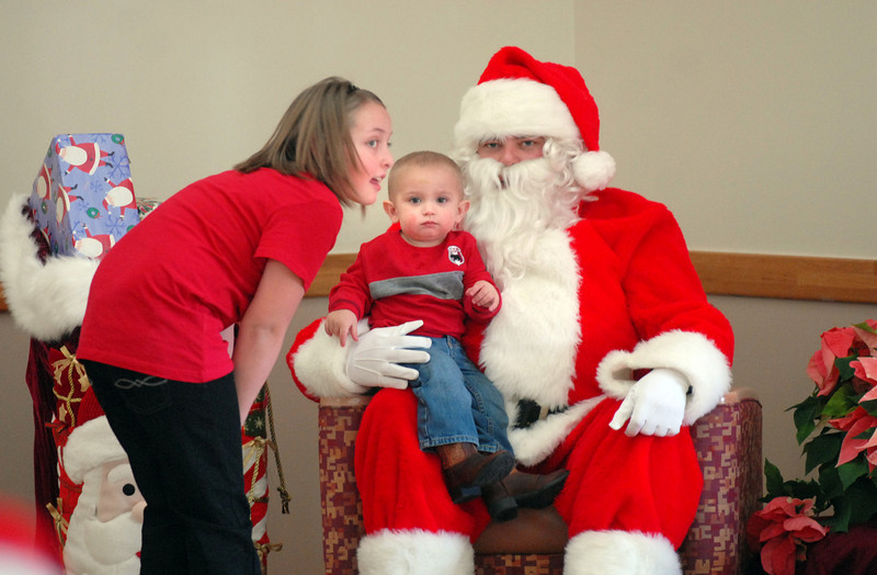 BE1205break08<br /> Kaitlyn Pattison, 11, left, chats with Santa and Reilly clapper, 18 months old, during the Broomfield Lions Club Breakfast with Santa on Saturday at the Broomfield Community Center.<br /> <br /> December 4, 2010<br /> staff photo/David R. Jennings