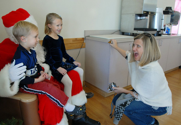 Peggy Heath, right, gets her children Joey, 5, left, and Krissy, 7, to smile as they talk to Santa at the 10th annual Broomfield Lions Club Breakfast with Santa at the Broomfield Community Center on Saturday.<br /> December 5, 2009<br /> Staff photo/David R. Jennings