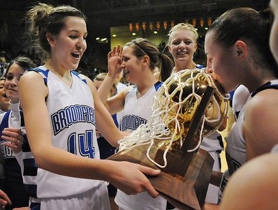 Katie Nehf, left, looking and holding Broomfield's 4th state championship trophy, is all smiles as Sarah Hix kisses the trophy after the Eagles defeated Longmont 55 to 47 for the class 4A championship at the Coors Events Center in Boulder on Friday.   March 12, 2010 Staff photo/David R. Jennings
