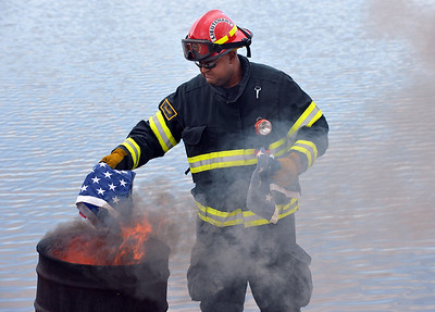 North Metro Fire Rescue Lt. Brian MIlls places a field of stars in the fire during Thursday's 8th Annual Flag Retirement Ceremony at the Community Park Amphitheater.   June 14, 2012  staff photo/ David R. Jennings