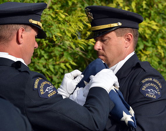 Broomfield Police Officers Todd Dahlbach, left, and Doug Whiles fold the 9/11 Memorial flag for retirement during Thursday's 8th Annual Flag Retirement Ceremony at the Community Park Amphitheater.<br /> <br /> June 14, 2012 <br /> staff photo/ David R. Jennings