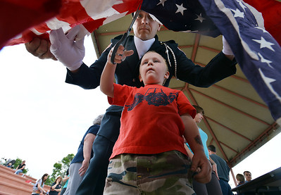 Ethan Burke, 4, with help from his father Jeff Burke with North Metro Fire Rescue, cuts the field of stars from the strips before they are burned during Thursday's 8th Annual Flag Retirement Ceremony at the Community Park Amphitheater.  June 14, 2012  staff photo/ David R. Jennings
