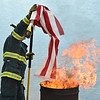North Metro Fire Rescue paramedic Randy Delaney places the strips from a flag into the fire during Thursday's 8th Annual Flag Retirement Ceremony at the Community Park Amphitheater.<br /> June 14, 2012 <br /> staff photo/ David R. Jennings