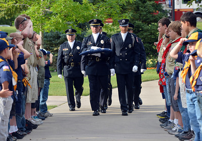 The combined Broomfield Police and North Metro Fire Honor Guard march the 9/11 Memorial flag to be retired as Cub and Boy Scout salute during Thursday's 8th Annual Flag Retirement Ceremony at the Community Park Amphitheater.  June 14, 2012  staff photo/ David R. Jennings