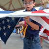 Cub Scout Hunter Liu, 7, cuts the field of stars from the strips of a flag before they are burned during Thursday's 8th Annual Flag Retirement Ceremony at the Community Park Amphitheater.<br /> <br /> June 14, 2012 <br /> staff photo/ David R. Jennings