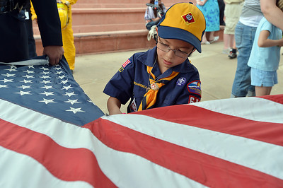 Cub Scout Hunter Liu, 7, cuts the field of stars from the strips of a flag before they are burned during Thursday's 8th Annual Flag Retirement Ceremony at the Community Park Amphitheater.  June 14, 2012  staff photo/ David R. Jennings