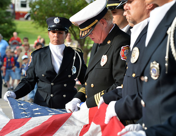 North Metro Fire Rescue Division Chief Kevin Sweeney cuts the field of stars from the strips of the 9/11 Memorial flag during Thursday's 8th Annual Flag Retirement Ceremony at the Community Park Amphitheater.<br /> <br /> June 14, 2012 <br /> staff photo/ David R. Jennings