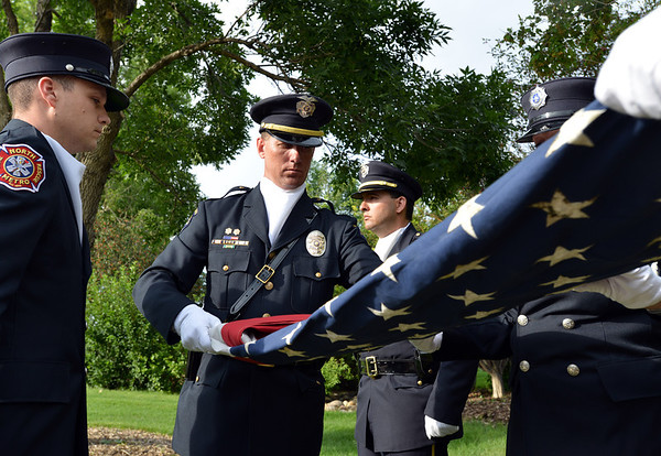 Broomfield Police Officer Todd Dahlbach folds the 9/11 Memorial flag to be retired during Thursday's 8th Annual Flag Retirement Ceremony at the Community Park Amphitheater.<br /> <br /> June 14, 2012 <br /> staff photo/ David R. Jennings
