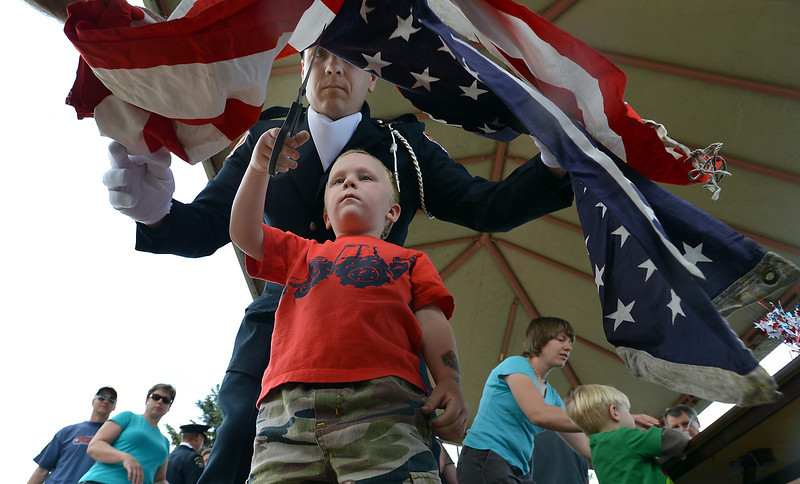 Ethan Burke, 4, with help from his father Jeff Burke with North Metro Fire Rescue, cuts the field of stars from the strips before they are burned during Thursday's 8th Annual Flag Retirement Ceremony at the Community Park Amphitheater.<br /> <br /> June 14, 2012 <br /> staff photo/ David R. Jennings