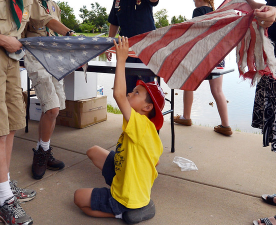 Stephen Wong, 6, holds the field of stars while his family cuts a flag being burned during Thursday's 8th Annual Flag Retirement Ceremony at the Community Park Amphitheater.<br /> <br /> June 14, 2012 <br /> staff photo/ David R. Jennings