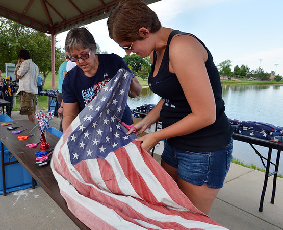 Tammy Brown, left, and her daughter Lauren Brown cut the field of stars from the strips of a flag during Thursday's 8th Annual Flag Retirement Ceremony at the Community Park Amphitheater.<br /> <br /> June 14, 2012 <br /> staff photo/ David R. Jennings