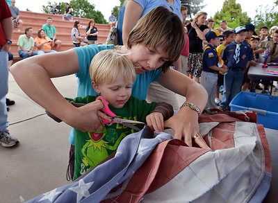 Benjamin Lind, 2 1/2, with the help of his mother Christy cuts the field of stars from the strips of a flag during Thursday's 8th Annual Flag Retirement Ceremony at the Community Park Amphitheater.  June 14, 2012  staff photo/ David R. Jennings
