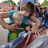 Benjamin Lind, 2 1/2, with the help of his mother Christy cuts the field of stars from the strips of a flag during Thursday's 8th Annual Flag Retirement Ceremony at the Community Park Amphitheater.<br /> <br /> June 14, 2012 <br /> staff photo/ David R. Jennings
